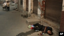 In this Oct. 31, 2019, photo, an Indian drug user lies unconscious by the side of a road in Kapurthala, in the northern Indian state of Punjab. Mass abuse of the opioid tramadol spans continents, from India to Africa. (AP Photo/Channi Anand)