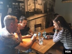 A father and his two daughters take a break from sightseeing at a Starbucks in Washington, D.C. (C. Maddux/VOA)