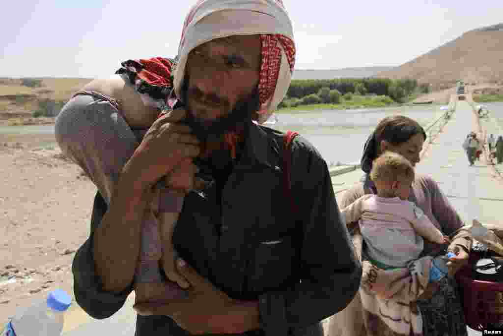 A man and his wife from the minority Yazidi sect, fleeing the violence in the Iraqi town of Sinjar, carry their children as they re-enter Iraq from Syria, Fishkhabour, Dohuk province, Aug. 14, 2014.