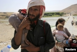 A man and his wife from the minority Yazidi sect, fleeing the violence in the Iraqi town of Sinjar, carry their children as they re-enter Iraq from Syria at the Iraqi-Syrian border crossing in Fishkhabour, Dohuk province, August 14, 2014.