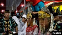 A bride's headdress is adjusted as she takes part in a mass wedding organized by the city government as part of New Year's Eve celebrations in Jakarta, Indonesia, December 31, 2017.
