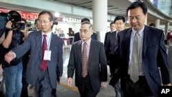 South Korea's top nuclear envoy Wi Sung-lac (C) is escorted to an entrance after arriving at the Capital International Airport in Beijing, China, September 20, 2011.