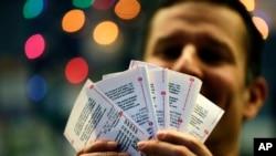 "Seorang pembeli memperlihatkan tiket lotere ""Mega Millions"" yang dibelinya saat hendak diundi hari Jumat, 13 Desember yang lalu (Foto: dok)."