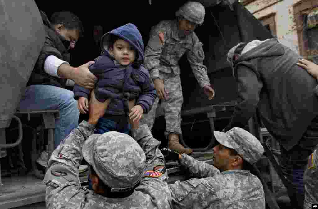 Vihaan Gadodia, de dos años es cargada en brazos de un miembro de la Guardia Nacional durante el rescate de su él y su familia de un edificio inundado en Hoboken, Nueva Jersey, el miércoles 31 de octubre. Muchos de los vecinos tuvieron que ser evacuados en camiones mientras la ciudad se recupera de las inundaciones. i