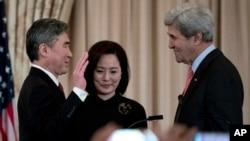 성김 신임 필리핀 주재 미국대사(왼쪽)가 3일 국무부에서 존 케리 국무장관(오른쪽)이 지켜보는 가운데 취임 선서를 하고 있다. 가운데는 김 대사의 부인 정재은 씨.