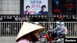 """Para pengendara sepeda melintasi ruang iklan yang kosong pernah diisi poster film animasi DreamWorks """"Abominable"""" sebelum dicopot di sebuah bioskop di Hanoi, Vietnam, 14 Oktober 2019. (Foto: Reuters)"""