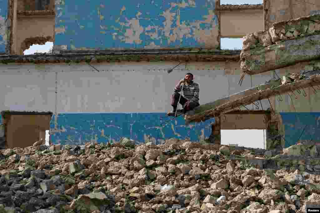 Irak Musul'da yıkık binanın enkazında oturan Iraklı