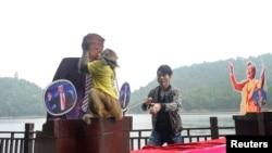 """Un singe porte un tee-shirt """"le roi de la prédiction"""" et embrasse la photo de Donald Trump, à Changsha, Chine, le 3 novembre 2016."""