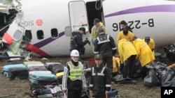 5일 타이완 여객기 추락 현장에서 구조요원들이 탑승자들의 가방과 소지품을 분류하고 있다.