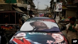 Pakistani supporters of former cricket star-turned-politician, and leader of Pakistan Tehreek-e-Insaf party, Imran Khan, ride a car decorated with his Khan's pictures, near a polling station in Rawalpindi, Pakistan, May 11, 2013.