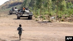 Young boy walks toward FARDC government forces tanks near the front line in Kanyaruchinya, 15 km from Goma, DRC, July 24, 2013.