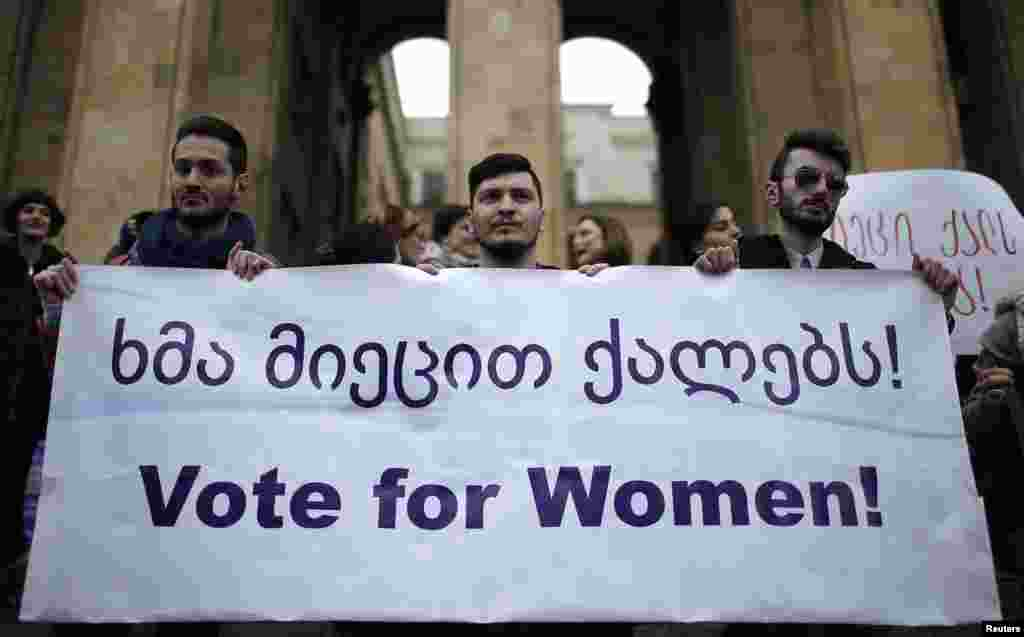 Men hold a banner during a protest demanding stronger women's political representation and engagement in parliament in front of the Parliament building on International Women's Day in Tbilisi, March 8, 2015.