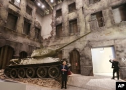 FILE - A woman stands in front of an exhibit in the Museum of the Second World War, an ambitious new museum under creation for nine years has opened its doors for a day to historians, museums and reporters in Gdansk, Poland, Jan. 23, 2017.