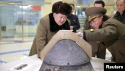 North Korean leader Kim Jong Un looks at a rocket warhead tip after a simulated test of atmospheric re-entry of a ballistic missile, at an unidentified location in this undated photo released by North Korea's Korean Central News Agency (KCNA).
