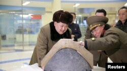FILE - North Korean leader Kim Jong Un looks at a rocket warhead tip after a simulated test of atmospheric re-entry of a ballistic missile, at an unidentified location in this undated photo released by North Korea's Korean Central News Agency.
