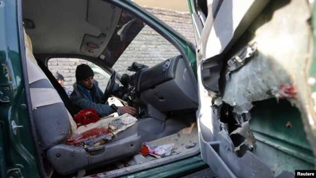 An Afghan policeman inspects the interior of a car belonging to the chief of police of Nimroz province, that was hit by a roadside bomb, in the Hadraskan district of Herat province, December 10, 2012.