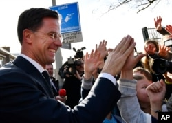 Dutch Prime Minister Mark Rutte gives high fives to children after casting his vote in the Dutch general election in The Hague, Netherlands, March 15, 2017.