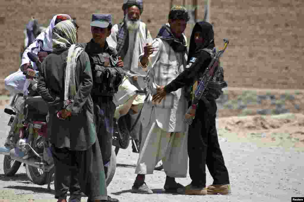 Afghan policemen search people near the house of Hashmat Karzai, the cousin of President Hamid Karzai, at the site of a suicide attack in Kandahar. President Karzai's powerful cousin Hashmat, a close ally of presidential candidate Ashraf Ghani, was killed in a suicide bomb attack, officials said.