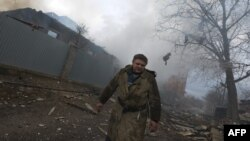 Un combatiente se aleja de varias casas destruidas en el bombardeo en la ciudad de Donetsk, al este de Ucrania.