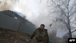 អ្នកពន្លត់អគ្គីភ័យដើរចេញពីផ្ទះមួយចំនួនដែលខូចខាតដោយគ្រាប់ផ្លោង នៅភាគខាងកើតប្រទេសអ៊ុយក្រែន នៅក្នុងទីក្រុង Donetsk កាលពីថ្ងៃទី៣ ខែកុម្ភៈ ឆ្នាំ២០១៥។