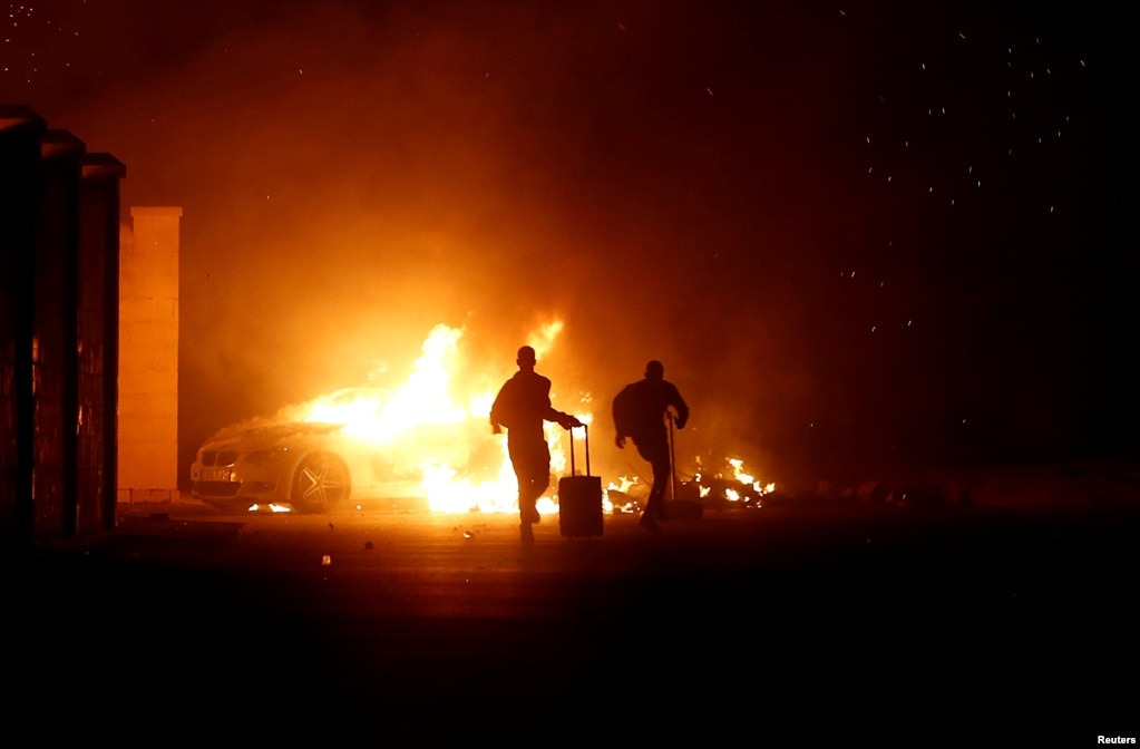 People run as a vehicle burns during riots at Hal Far Open Centre migrant camp in Hal Far, Malta, Oct. 21, 2019.