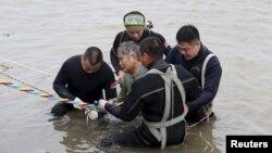 Una mujer es ayudada a salir del agua luego de naufragar con el barco Jianli o Oriental Star en la provincia Hubei de China.