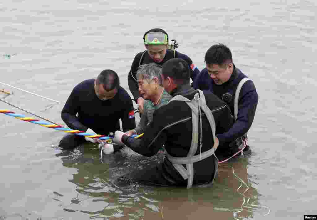 A woman is helped by divers from a sunken ship in Jianli, Hubei province, China, June 2, 2015. Divers pulled the 65-year-old woman from the hull of the passenger ship carrying 458 people that capsized on China's Yangtze River and others could still be alive, state media said on Tuesday.