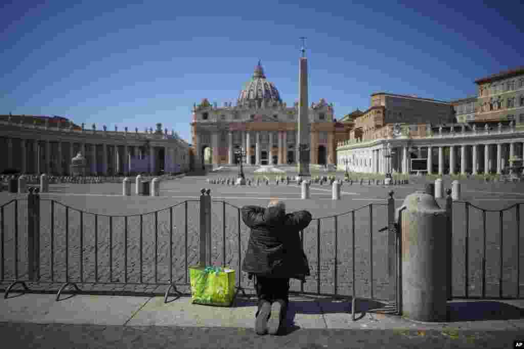 یک مرد با زانو زدن پشت نردههای کلیسای سنت پیتر، در واتیکان دست به دعا برداشته است.