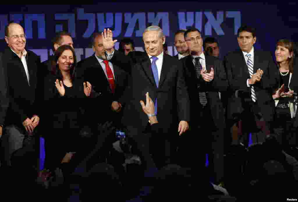 Israel's Prime Minister Benjamin Netanyahu waves to supporters as he stands at Likud party headquarters in Tel Aviv, January 23, 2013.