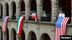 FILE - U.S. and Mexican flags are displayed at the National Palace in Mexico City, May 2, 2013.
