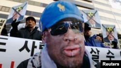 A protester wearing a mask depicting former U.S. basketball star Dennis Rodman, attends a rally in central Seoul, South Korea, Jan.8, 2014, denouncing Rodman's visit to North Korea and North Korean leader Kim Jong Un on Kim's birthday.
