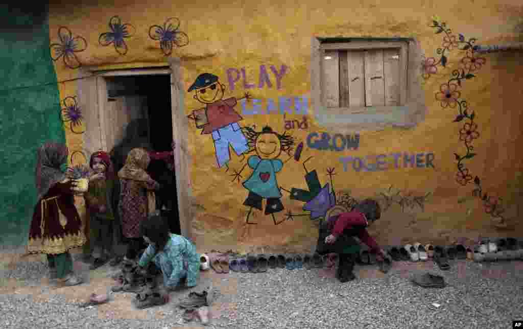 Anak-anak sekolah mencari-cari sepatunya sementara yang lain masuk kelas di tengah kunjungan petugas vaksin polio ke daerah miskin di pinggir kota Islamabad (31/1). (AP/Muhammad Muheisen)