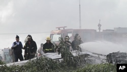 Firemen spray fire retardant on plane L410 of Noar Airlines that fell near Boa Viagem beach in Recife, the capital of the northeastern state of Pernambuco, July 13, 2011