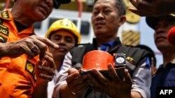 Para petugas tampak menunjukkan sebagian dari kotak hitam Lion Air no penerbangan JT610 yang bernasib naas, yaitu perekam data penerbangan (FDR), yang berhasil diangkat dari Laut Jawa, dalam operasi pencarian di perairan lepas pantai Karawang tanggal 1 November 2018 (foto: Pradita Utama/Detikcom/AFP)