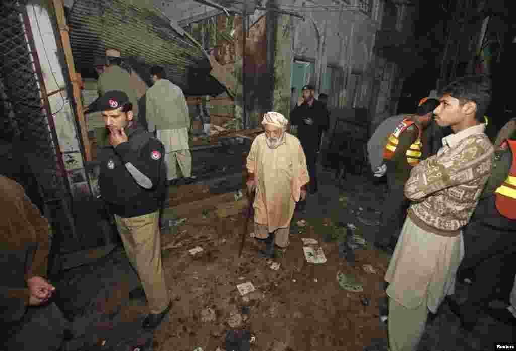 پولیس اہلکار اور امدادی کارکن دھماکے کی جگہ پر کھڑے ہیں