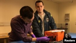 National Transportation Safety Board engineers Ben Hsu, left, and Sean Payne examine the recorder from the lead locomotive involved in the derailment of Amtrak train 501 in DuPont, Washington, at the NTSB lab in Washington, D.C., Dec. 20, 2017.