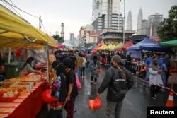 Para pengunjung bazaar mengenakan masker saat belanja makanan menjelang buka puasa di bulan suci Ramadan, di tengah pandemi COVID-19, di Kuala Lumpur, Malaysia, 15 April 2021. (REUTERS/Lim Huey Teng)