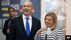 FILE - Israeli Prime Minister Benjamin Netanyahu stands by his wife Sara as she casts her ballot at a polling station in Jerusalem, Jan. 22, 2013.