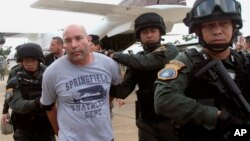 FILE - Joseph Hunter, second from left, a former U.S. Army sniper, was arrested in Bangkok, Thailand, Sept. 26, 2013. Hunter and two other American ex-soldiers were convicted Wednesday in the contract killing of a real estate agent in the Philippines for an international crime boss.