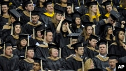 FILE - Students wait to be called for their degree during the University of Connecticut's Graduate School commencement ceremony.