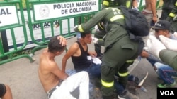 A Colombian police officer helps men who were hurt in clashes at the Simon Bolivar Bridge on the Colombia-Venezuela border near Cucuta.