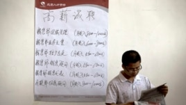 Chinese man reads the employment newsletters at a job fair held at the China International Exhibition Center in Beijing.