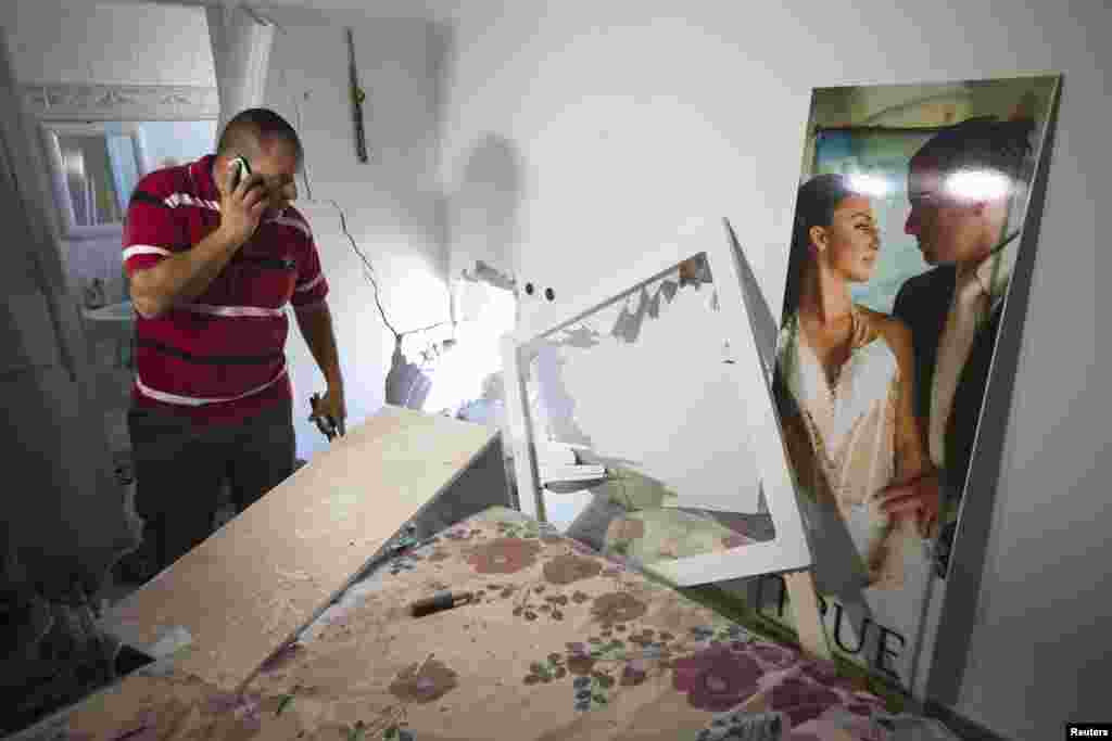 Avihai Jorno inspects the damage to his home after a rocket fired by Palestinian militants in Gaza landed in the southern town of Sderot, July 3, 2014.