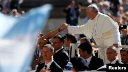 Pope Francis greets people as he arrives to lead his Wednesday general audience in Saint Peter's square at the Vatican, Sept. 18, 2013.