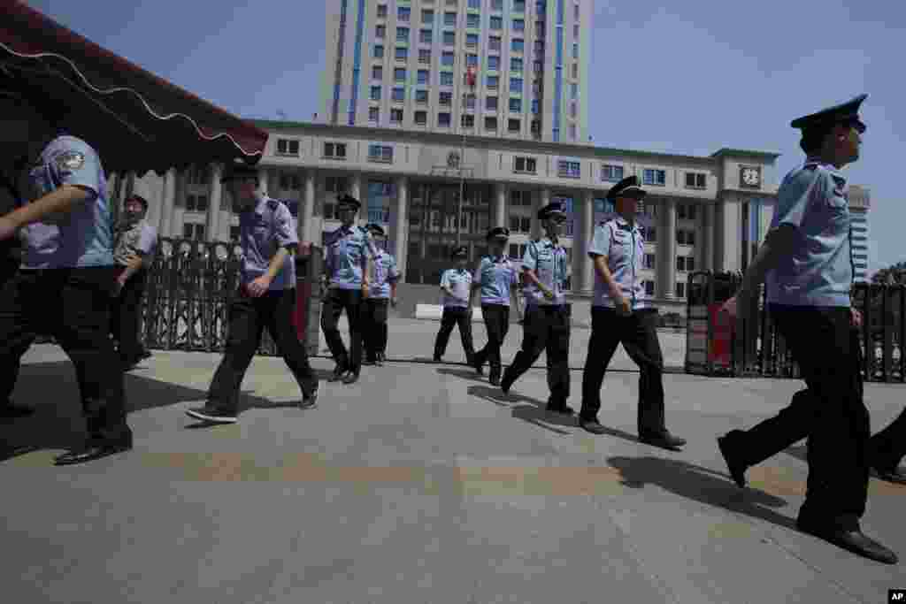 Chinese police officers march out of the Jinan Intermediate People's Court in Jinan in eastern China's Shandong province, August 21, 2013.