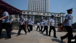 FILE - Chinese police officers march out of the Jinan Intermediate People's Court in Jinan in eastern China's Shandong province.