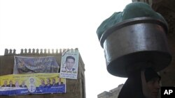 """A woman walks near an election poster of Egypt's Muslim Brotherhood """"The Freedom and Justice Party'"""" in the old city of Cairo December 2, 2011."""