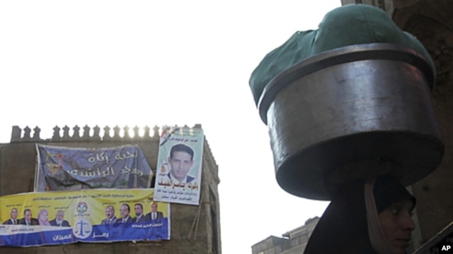 "A woman walks near an election poster of Egypt's Muslim Brotherhood ""The Freedom and Justice Party'"" in the old city of Cairo December 2, 2011."