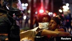 Deux femmes manifestent regardant un officier de police à Charlotte en Caroline du Nord le 21 septembre 2016.