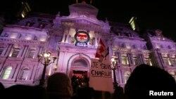 Des personnes participant à une veillée, près de l'Hôtel de ville de Montréal, pour rendre hommage aux victimes de l'attaque contre l'hebdomadaire satirique Charlie Hebdo à Paris, 7 janvier 2015.